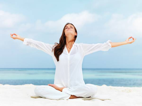 Beautiful woman stretching during meditation on the beach